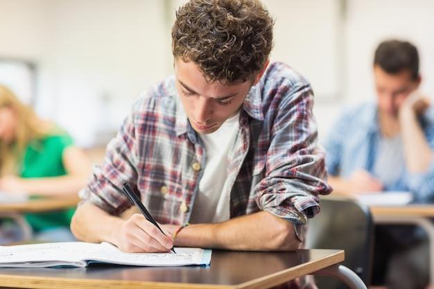 Мужской студент с другими, записывающий заметки в классе