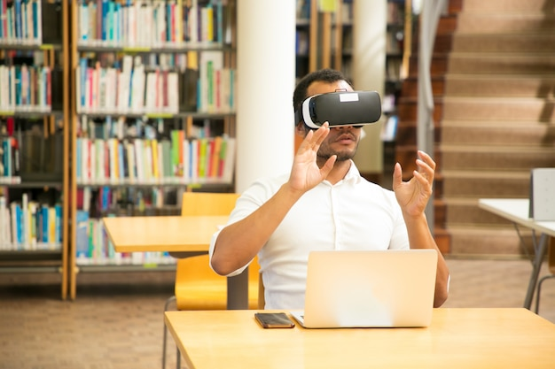 Male student working with vr simulator in library