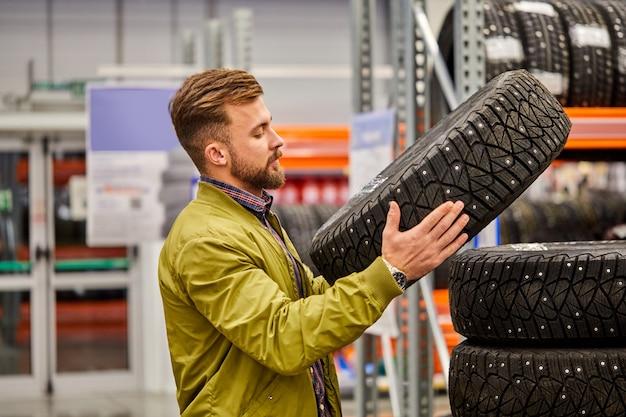 市場で車のタイヤを勉強している男性、タイヤを見てカジュアルウェアスタンドの男、選択をします。ショッピングタイム