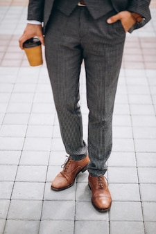 Male suit close up holding coffee in hand