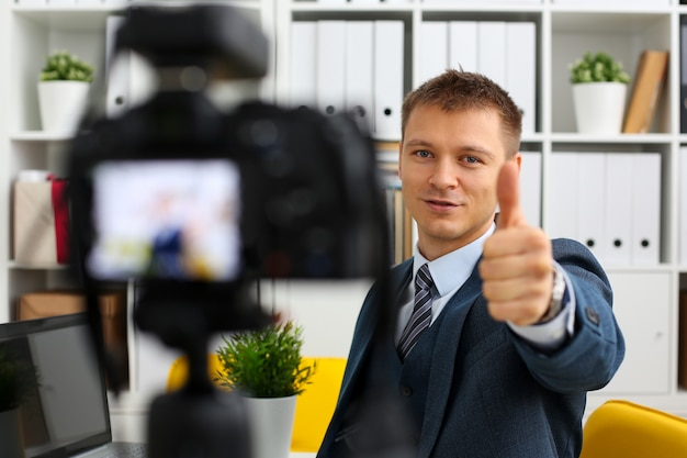 Male in suit and tie show confirm sign arm making promo videoblog or photo session in office camcorder to tripod portrait.