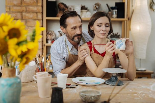 男性のサポート。土鍋で働く妻をサポートしている間、ひげを生やした男性は非常に役立つと感じています