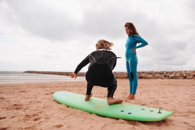 Мужской учитель серфинга учит молодую кавказскую женщину заниматься серфингом на пляже