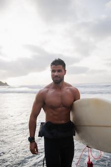 해질녘 해변에서 서핑 보드를 들고 있는 남성 서퍼는 젊습니다. 웃고 있는 매력적인 남자가 재미있고 익스트림 스포츠를 하는 것 - 밀레니얼 세대 개념의 행복 - 그의 얼굴에 초점을 맞춥니다.