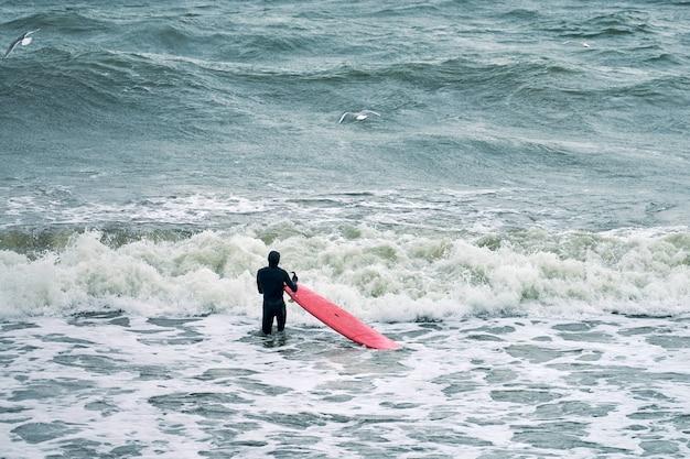 Мужчина-серфер в черном купальнике в океане с красной доской для серфинга в ожидании большой волны. теплый день, прекрасная морская вода, природа. концепция спорта и активного отдыха.