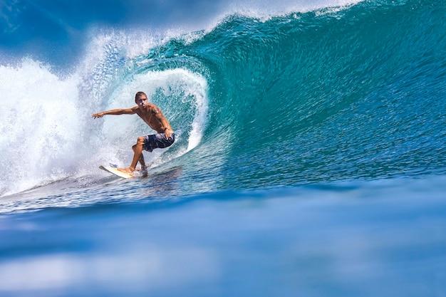 Мужчина-серфер на синей волне в солнечный день