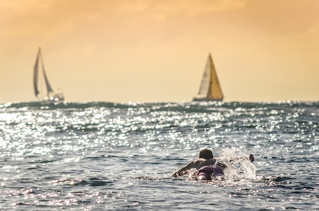 Male surfer paddling out at sunset in hawaii with sailboats in the background