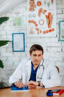 Male surgeon doctor in medical uniform with stethoscope posing in the cabinet.