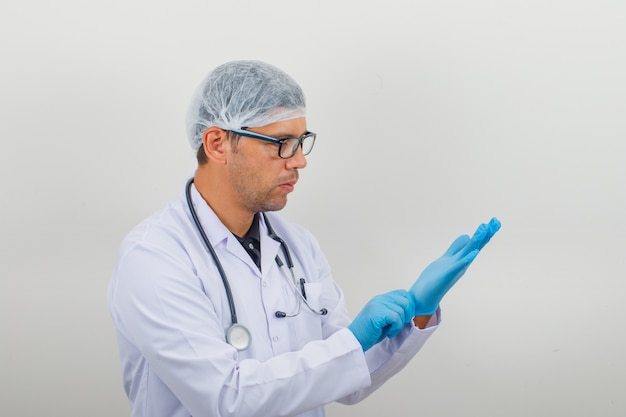 Male surgeon putting on glove in medical white robe