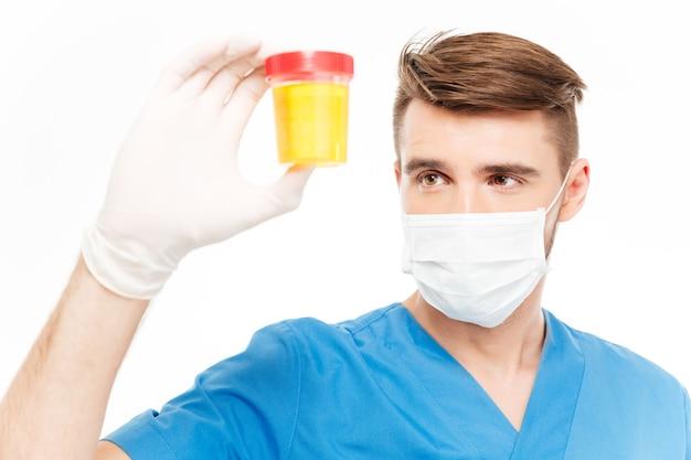 白い背景で隔離の尿サンプルのボトルを保持しているマスクを持つ男性外科医
