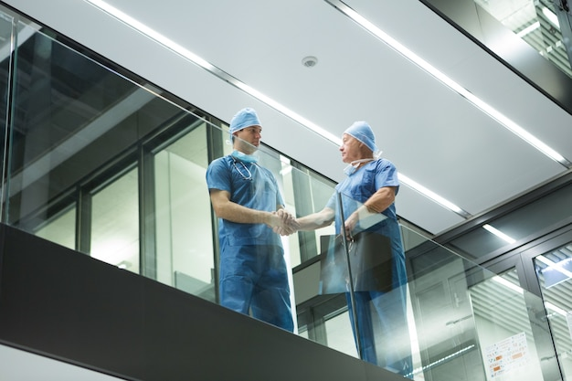 Male surgeons shaking hands in corridor