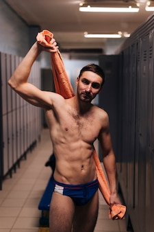 Male swimmer drying with towel