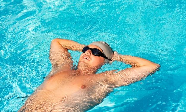プールに浮かぶ男性スイマー