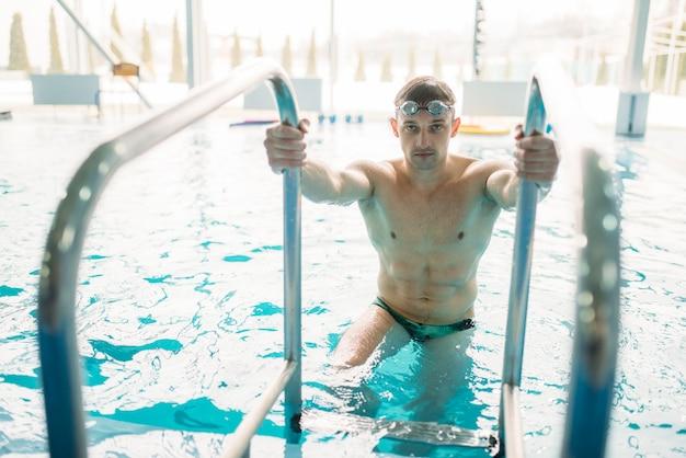 ゴーグルの男性水泳選手がプールから登ります。アクアスポーツトレーニング、健康的なライフスタイル