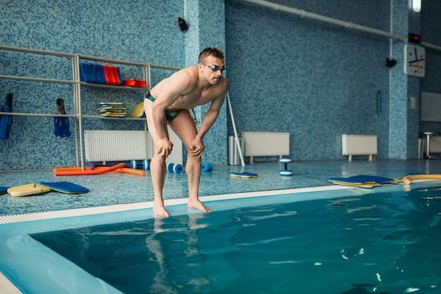 男性スイマーは水に飛び込む準備をします