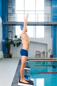 Male swimmer ready to jump in pool