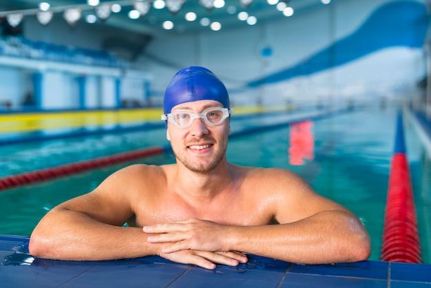 Мужской пловец, стоящий на краю бассейна
