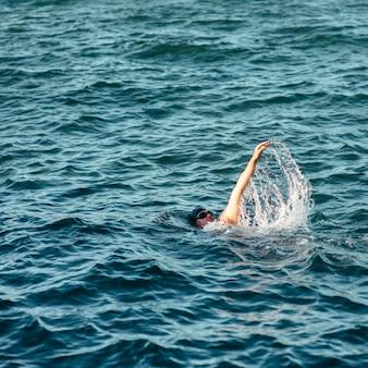 コピースペースと水で泳ぐ男性スイマー