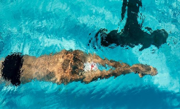 Nuotatore maschio che nuota nella piscina di acqua