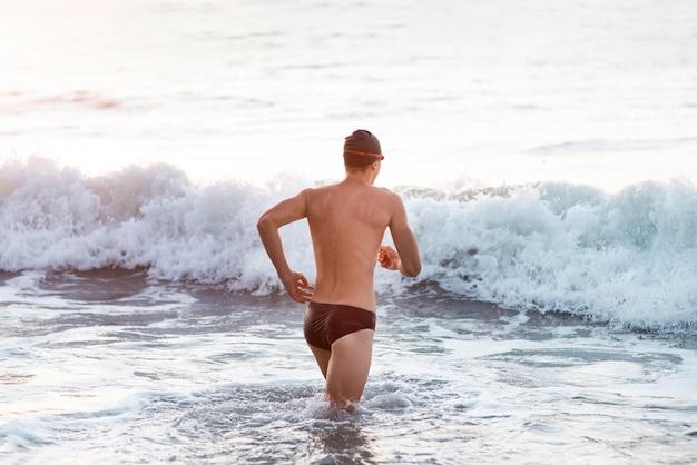 海に行くゴーグルとキャップを持つ男性のスイマー