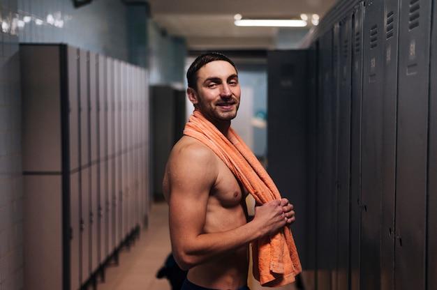 Male swimmer with towel in locker room
