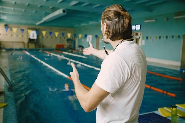 スイミングプールのそばに立っている男性の水泳コーチ。彼は学生を正すためにまっすぐな手を見せています。水泳技術、プロ。
