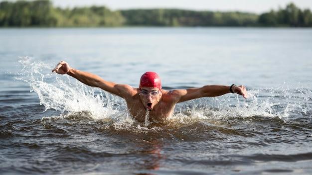 Мужчина купается в озере