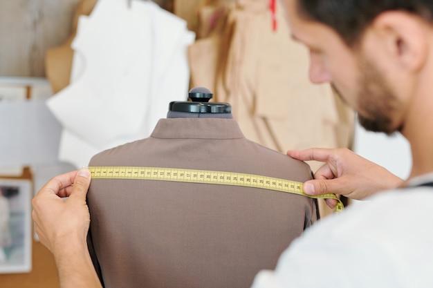 Мужской портной измеряет заднюю часть новой куртки на манекене, работая над незавершенным заказом клиента