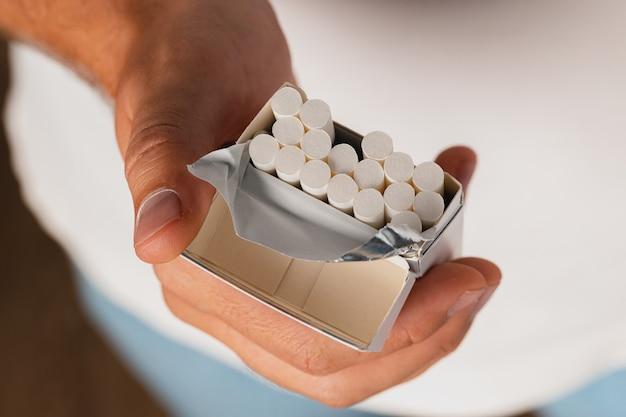 たばこパックからたばこを取り出す男性