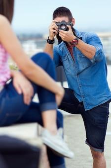 Male taking photo of posing girl