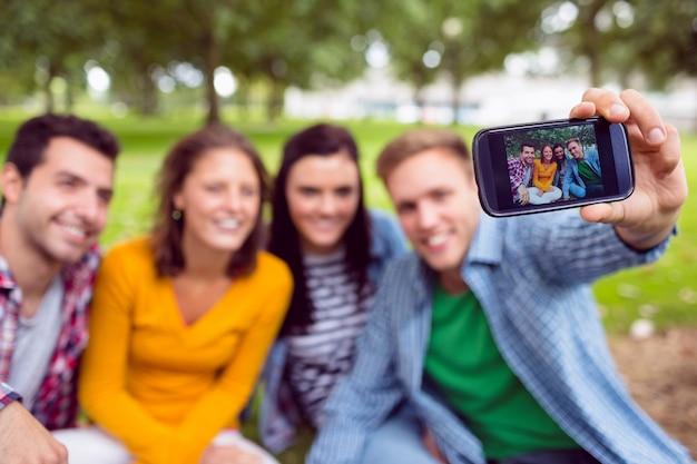 公園のカレッジの友達と写真を撮っている男性