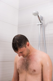 Male taking a shower, standing under flowing water in  the bathroom