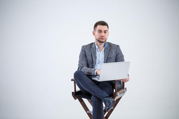 文書を勉強している椅子に座っている男性教師ディレクタービジネスマン。彼はノートパソコンの画面を見ています。新規事業プロジェクト。