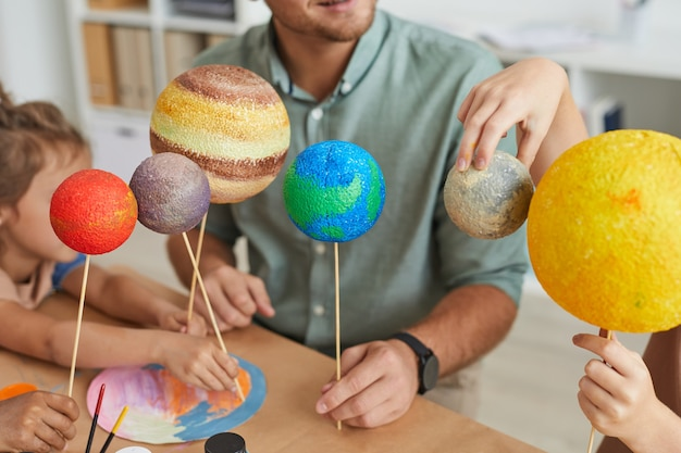 Male teacher holding planet models while working with group of children in art and craft lesson