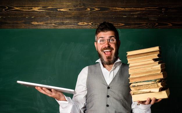 Учитель-мужчина держит традиционный учебник и читает книгу электронных книг против электронной книги электронной библиотеки электронной книги