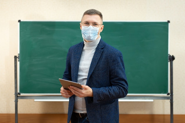 A male teacher in a medical mask stands at the blackboard in the classroom