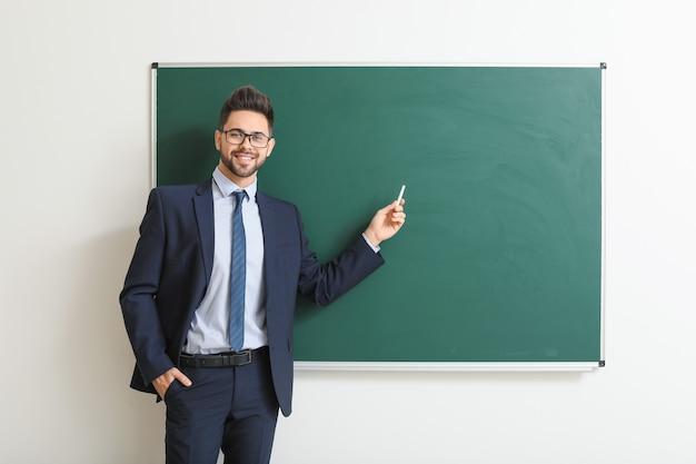Male teacher near blackboard in classroom
