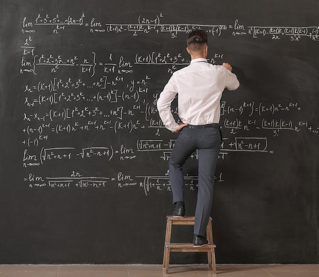 教室の黒板の近くの男性教師