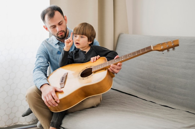 Male teacher tutoring child at home for guitar lessons
