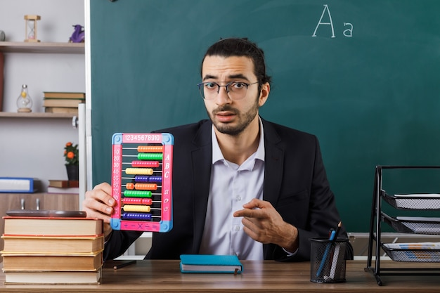 Male teacher wearing glasses holding abacus sitting at table with school tools in classroom