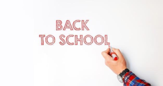 手に赤いマーカーを持った男性教師が白い黒板に「学校に戻る」というテキストを書いています。学年の初め
