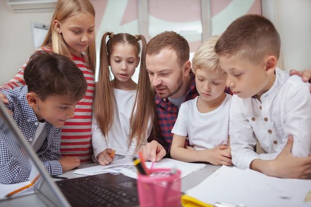 就学前の子供と一緒に働く男性教師