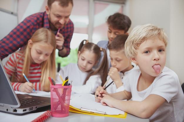 Male teacher working with children at preschool
