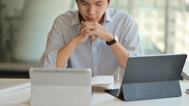 Учителя-мужчины готовятся преподавать онлайн с помощью цифрового планшета.