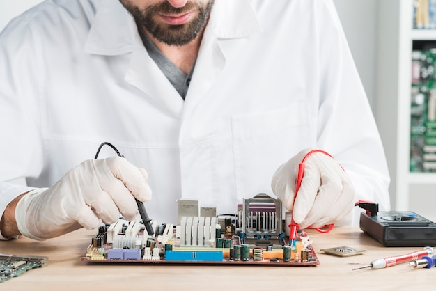 나무 책상에 디지털 멀티 미터와 컴퓨터를 확인하는 남성 기술자