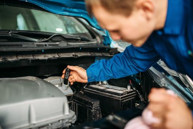 Техник-мужчина проверяет уровень тормозной жидкости в автомобиле