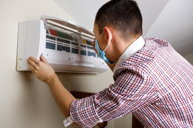 Мужской техник, чистящий кондиционер в помещении
