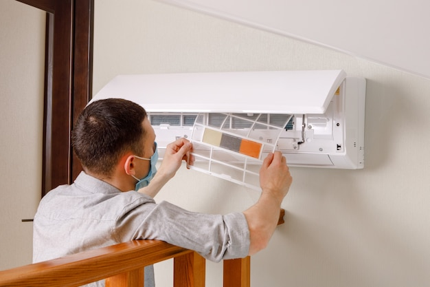 Male technician cleaning air conditioner indoors