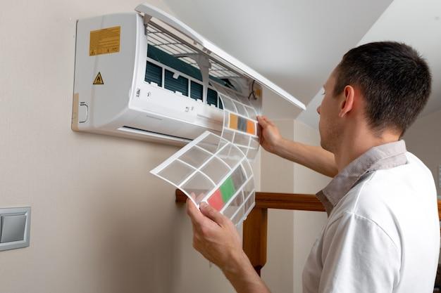 室内でエアコンを掃除する男性技術者