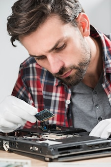 Male technician examining laptop ram